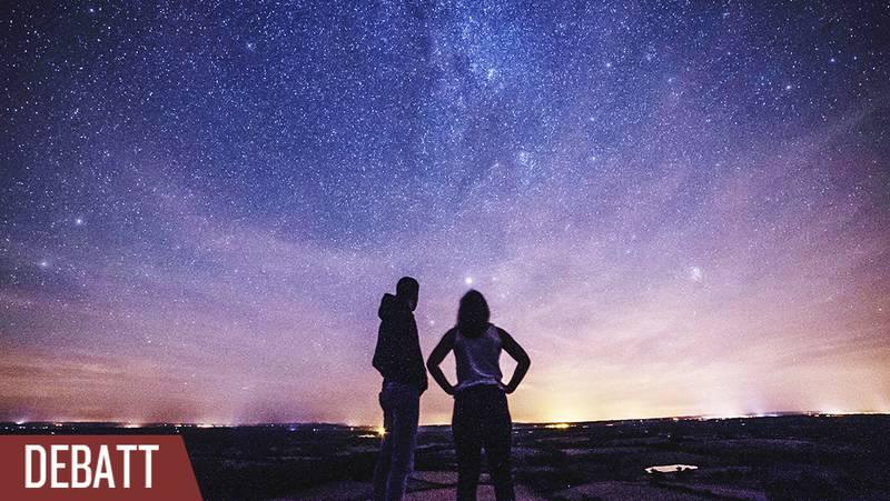 Två personer tittar upp mot stjärnhimlen.