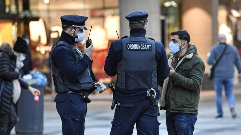 Ordningsvakter kontrollerar att förbipasserande bär munskydd. Bilden är från Dortmund i västra Tyskland.