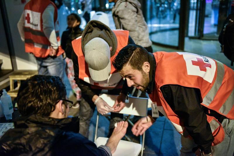 Frivilliga från Röda korset hjälper nyanlända flyktingar vid Malmö central 2015.