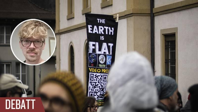 En folksamling demonstrerar mot coronarestriktioner med plakat om att jorden är platt.