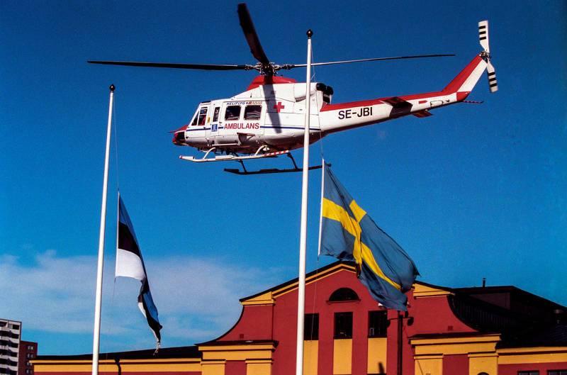 En ambulanshelikopter flyger över Estlines huvudkontor i Frihamnen i Stockholm 28:e september 1994 där estniska och svenska flaggan är hissade på halv stång i samband färjeolyckan M/S Estonias förlisning ute på Östersjön tidigare på natten.