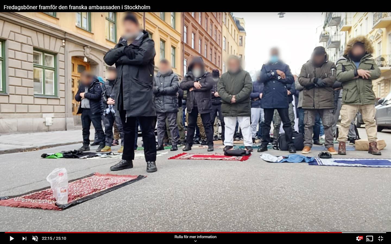 Muslimska män protesterar utanför den franska ambassaden i Stockholm.