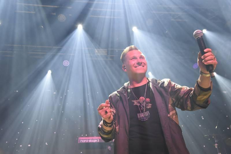 Glad sångare på festivalscen med mikrofon i handen.