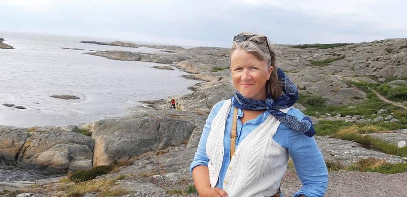 Anna-Sophia Bonde framför ett klipplandskap mer mot en havsvik.