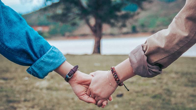 Två personer håller varandras händer framför ett stort träd.