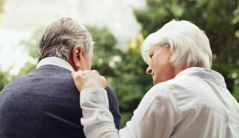 Ett äldre par. Kvinna tar hand om man.