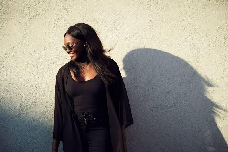 Somrig halvkroppsbild på sångerskan Faith Kakembo framför en vägg.