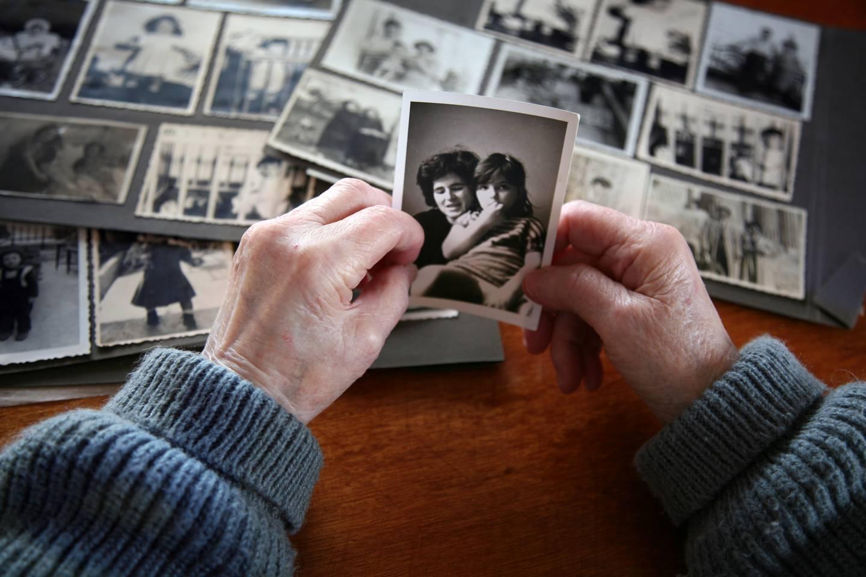 En kvinna tittar på ett fotografi. En mamma med sitt barn syns på fotografiet.