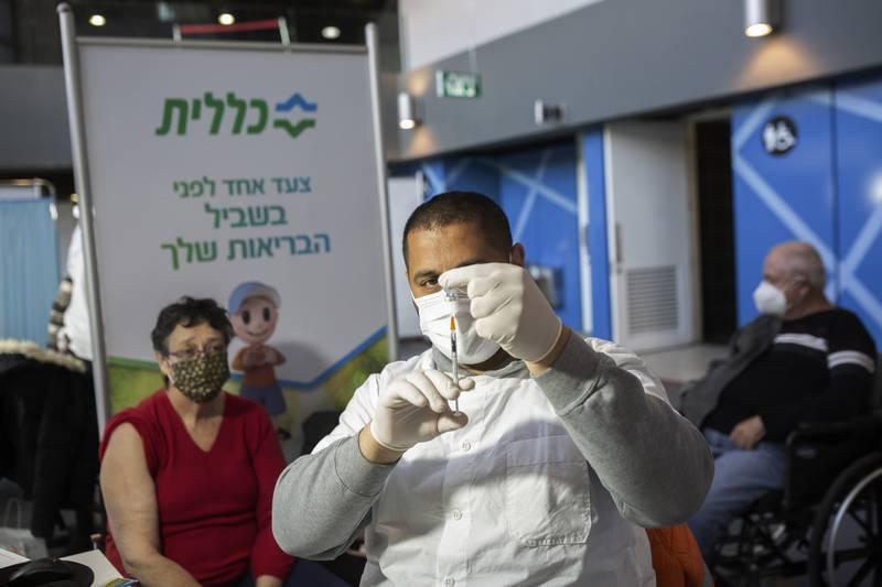 Vaccinationsdoser ges på löpande band på en vaccinationsplats utanför Jerusalem.