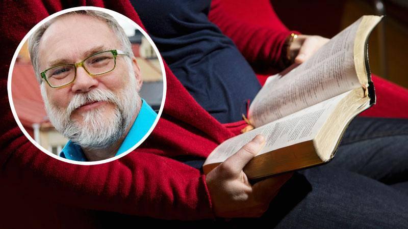 Person sitter i en fåtölj och läser Bibeln. Infälld bild på Ray Baker.