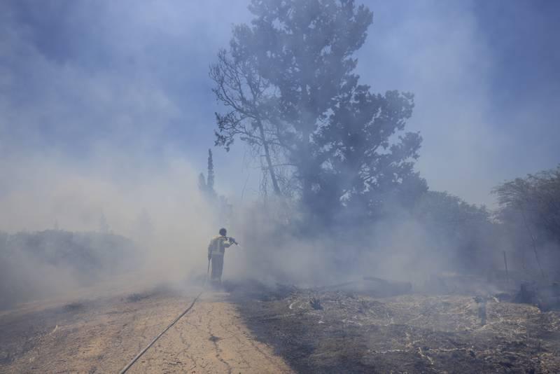 En israelisk brandman försöker släcka en brand som orsakats av en brandballong som skickats från Gaza den 15 juni 2021. Arkivbild.