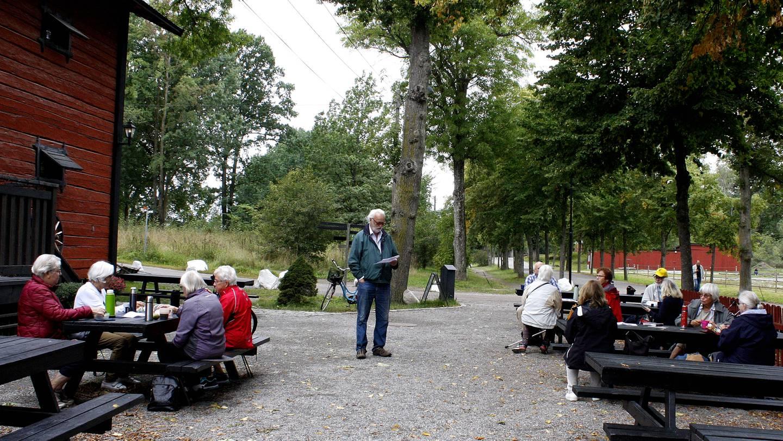 Medlemmar i RPG Järfälla sitter vid utebord. I mitten står Urban Norstedt och pratar.