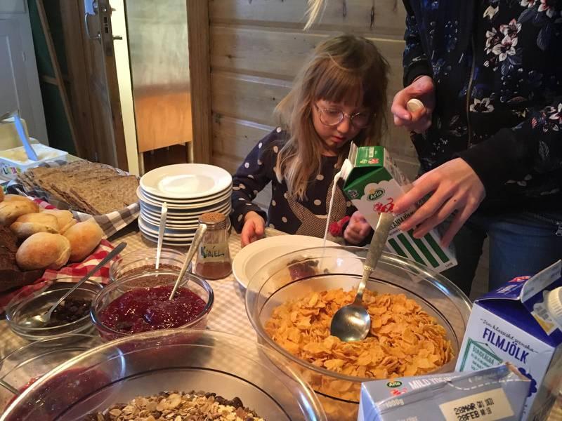 Gästerna på gården njuter av hembakat bröd till frukosten. Här är det Elsie, 5 år, som laddar med gröt inför en dag i skidbacken.