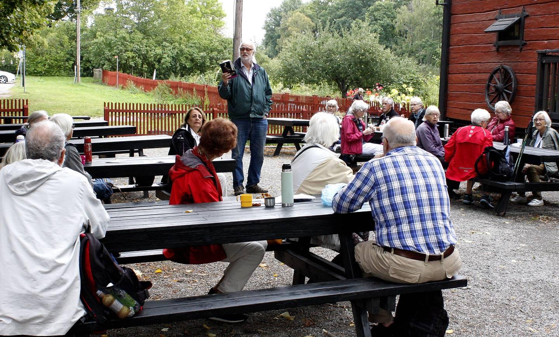 Deltagare i RPG Järfälla sitter runt utebord och tittar på Urban Norstedt som håller upp en bok.