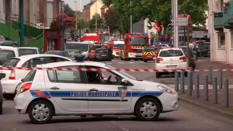Polisbil och avspärrningar utanför en kyrka i Saint-Étienne-du-Rouvray i Normandie i norra Frankrike där flera personer hållits som gisslan.