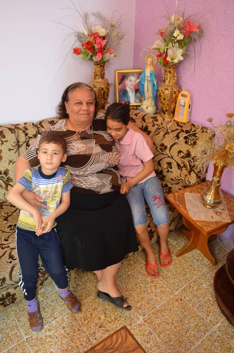 Nazran Aziz med två av sina barnbarn. På fotot i bakgrunden hennes son som blev mördad i de strider som blossade upp efter Saddam-regimens fall.