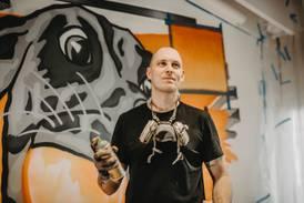 Victor målar graffiti av sin tro på Gud