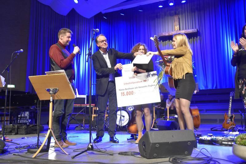 Urban Thoms, från tidningen Dagen och Roland Utbult delar ut stipendiet till Hanna och Alexandra.
