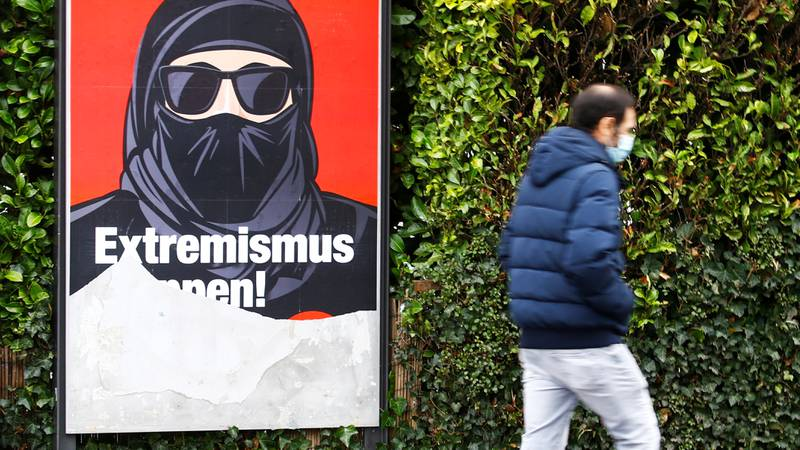 """A partially torn poster of the initiative committee against wearing the Burka (Verhuellungsverbot) reading """"Stop extremism! Veil ban -Yes"""" is seen in Zurich, Switzerland February 2, 2021. On March 7 Switzerland's voters will decide about a nationwide veil ban.  REUTERS/Arnd Wiegmann  X90184"""